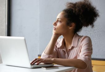 Close up portrait of a young african american woman looking out window when working on laptop