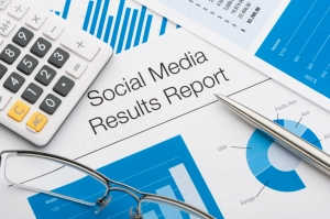 Close up of a social media results report with pen and calculator