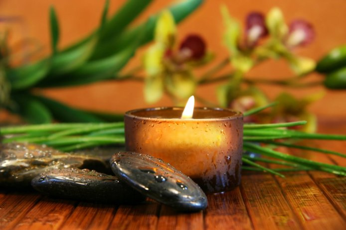 Image Source: Amber candle and spa stones with orchid  on bamboo